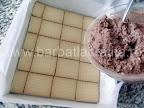 Prajitura preparare reteta - intindem crema de gris cu cacao peste primul strat de biscuiti