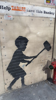 Image by Banksy. Image of a boy using a mallet.