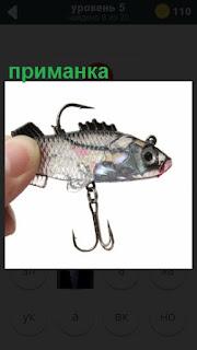 в руках держат приманку для рыбной ловли с крючком