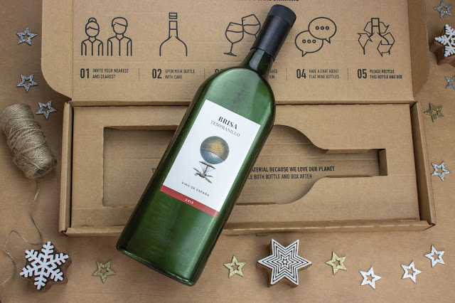 A dark green plastic wine bottle which is bottle shaped but flat on top of a protective cardboard box for posting.