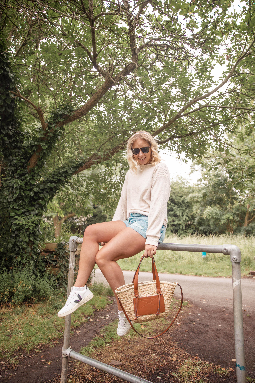 Rachel Emily wearing a beige jumper, denim shorts and the mango tan basket bag whilst sitting