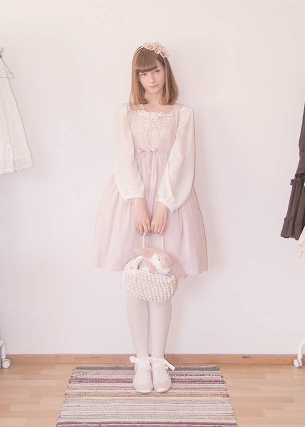 a girl dressed in a pink innocent world lolita dress holding a vintage bag.
