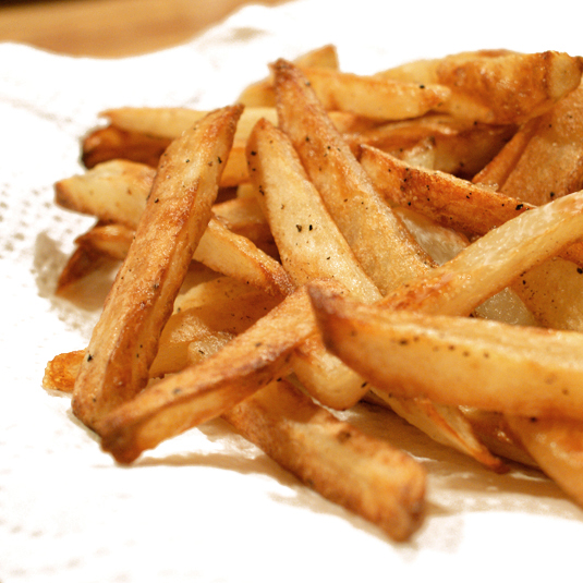 Close up side view of oven baked french fries on a paper towel.