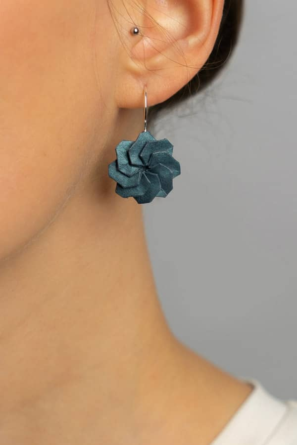turquoise circular origami earring with silver ear wire on model