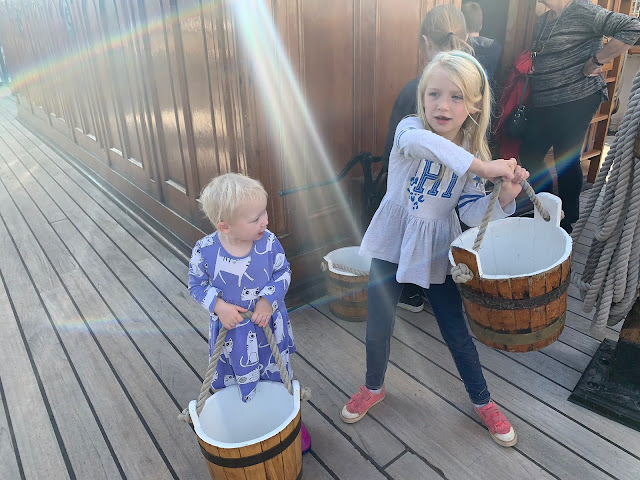Two children carrying wooden buckets