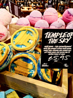 A group of round yellow and blue bath bombs with an airplane design in the middle in a light brown wooden square box with a black rectangular label with temple of the sky on a bright background