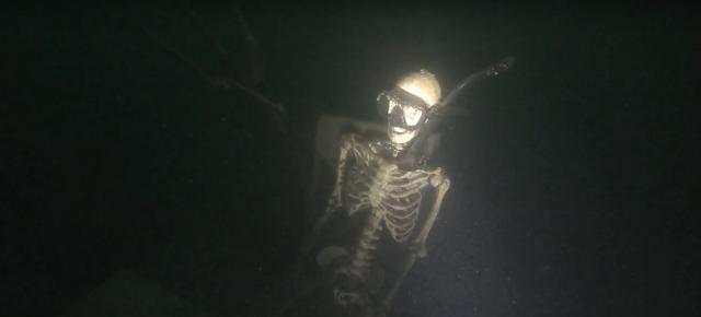 Mergulhadores encontram 4 esqueletos sentados à mesa no fundo escuro de um lago