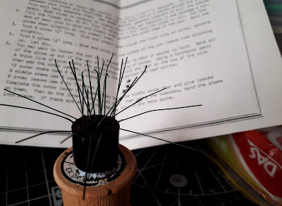 1/12 scale miniature plant kit with bare stems in a plant pot filled with 'soil' on top of a cotton reel, with a packet of air-drying clay to one side and a set of instructions behind.