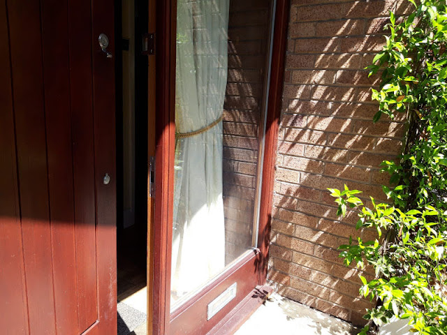 A partially opened wooden front door.  To the right of the door is a glass window, and to the right of the photo are green leafy plants