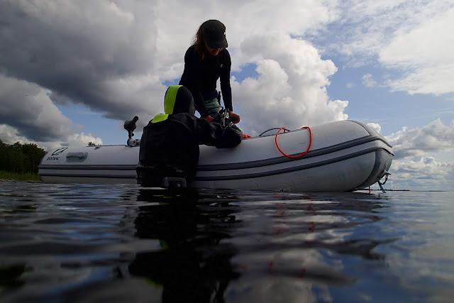 Sukeltaja kumiveneen vieressä, työkaveri veneessä.