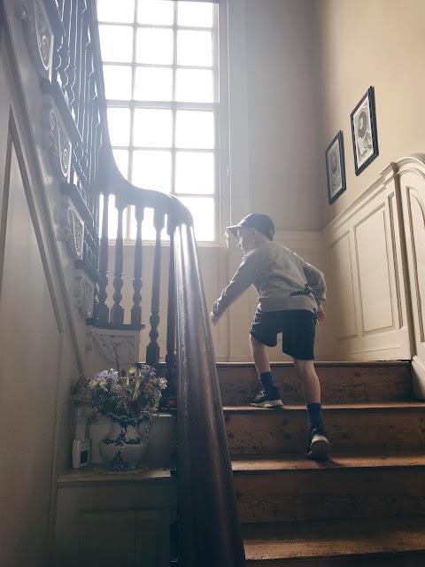 Little boy climbing grand stairs