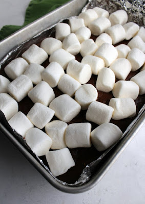 pan of half cooked s'mores bars with bright white marshmallows on top