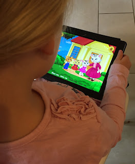 Screen from the back of a young girl watching the KidloLand app 3 Little Kittens song