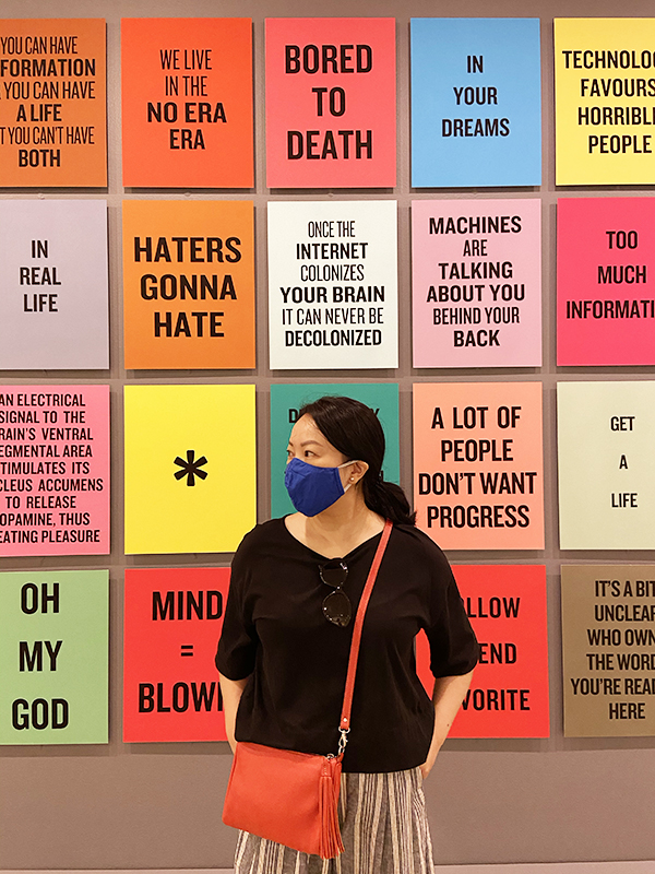 Solo Lisa stands in front of a portion of Douglas Coupland's 'Slogans for the 21st Century'.