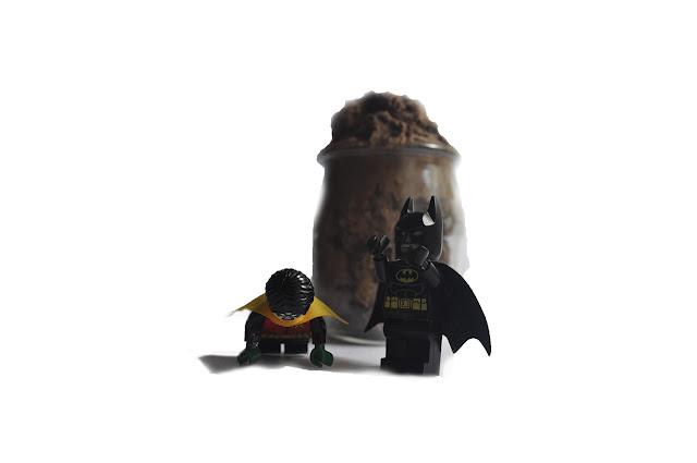 Robin de lego es castigado por Batman de lego a realizar flexiones, detrás una mousse de chocolate