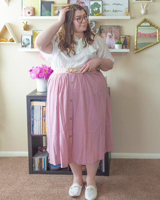 An outfit consisting of a white flounce sleeve blouse tucked into a muted pink button down midi skirt and white mules.