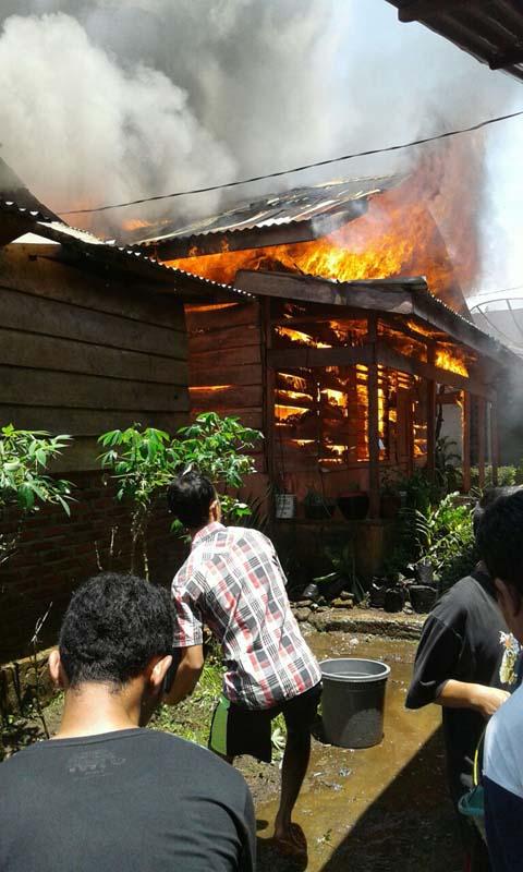 Puluhan warga berusaha memadamkan api yang membakar rumah milik warga.