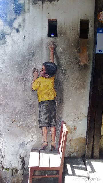 little boy reach up street art penang