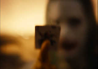 Blurry shot of Joker holding a Joker playing card.