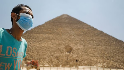 "An Egyptian young man wearing mask in front of the Great Pyramid  of Giza due to COVID-19 ""Reuters"""