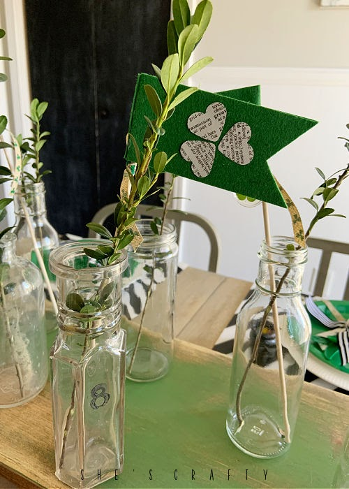 St Patrick's Day Table Centerpiece - bottles stamped with numbers, greenery and st patricks flags