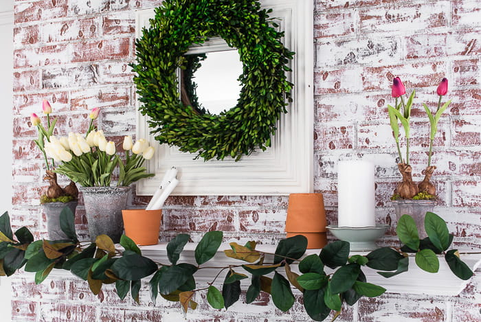 Spring mantel with magnolia garland, faux tulips, flower pots and boxwood wreath