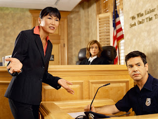 Photo of a female lawyers and a female judge with a witness in court.