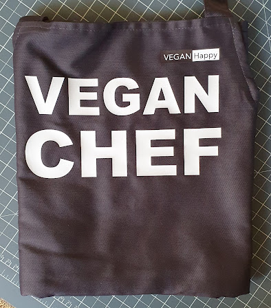 Vegan Happy apron with Vegan Chef written on it  folded before use