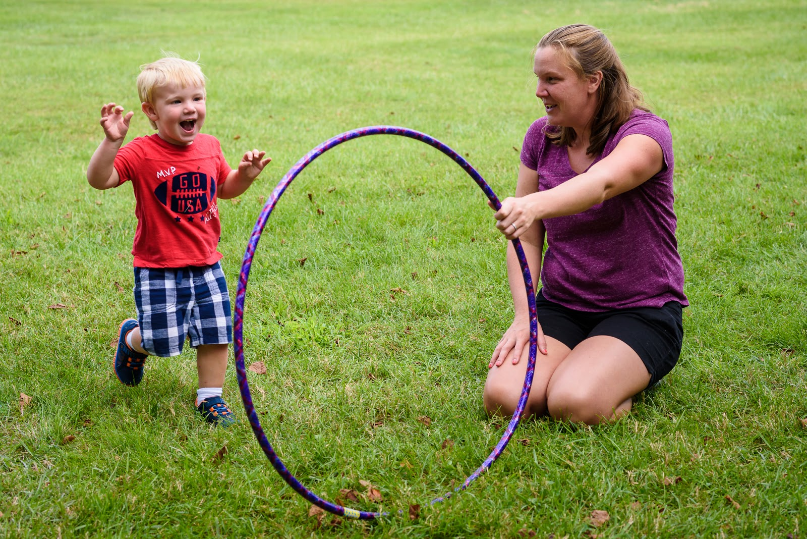 boy about to run through hula hoop held by Mom Music Together Vivo! Park Playalong © Diana Sherblom Photography