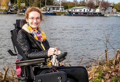 Hannah, a young woman with curly aburn hair and glasses sitting in her powerchair by the river. She is wearing a leather jacket, a mustard flowery scarf and black leggings.