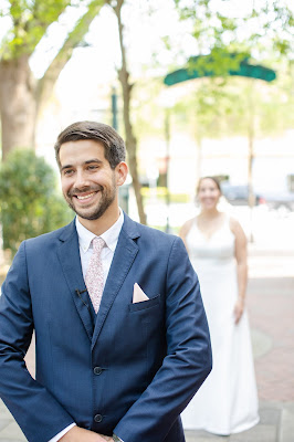 groom smiling with bride behind for first look
