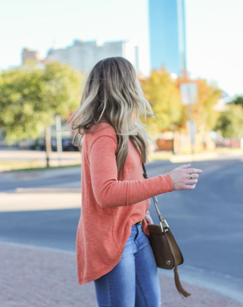 blonde girl spinning in orange sweater
