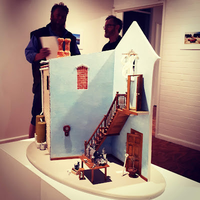 One-twelfth scale model of a two-story building on display in a gallery with teo people in discussion behind it.
