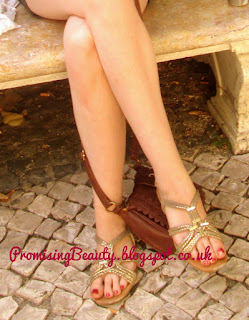 Legs with gold sandals and cobbles.