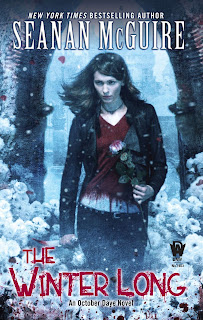 A pale woman with long dark hair walks through a snowy archway amid white flowers, holding a white rose dripping blood in her left hand, a blood knife held by her right side. She's wearing a dark jacket and jeans, her shirt appears red at first but the white along the edge reveals it to be almost completely soaked in blood.