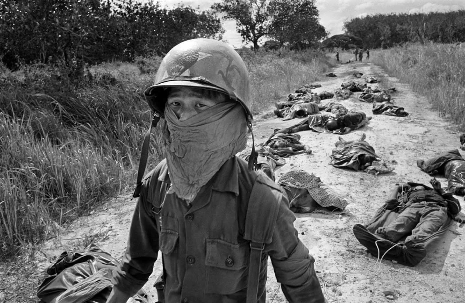 A Vietnamese litter bearer wears a face mask to keep out the smell as he passes the bodies of U.S. and Vietnamese soldiers killed in fighting against the Viet Cong at the Michelin rubber plantation, about 45 miles northeast of Saigon, on November 27, 1965.