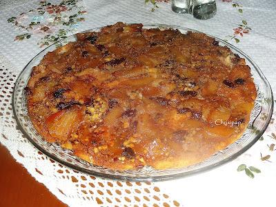 κέικ με μήλα σε μία πολύ ωραία γιάλινη πιατέλα πάνω σε τραπέζι που είναι στρωμένο με κεντητό τραπεζομάντηλο