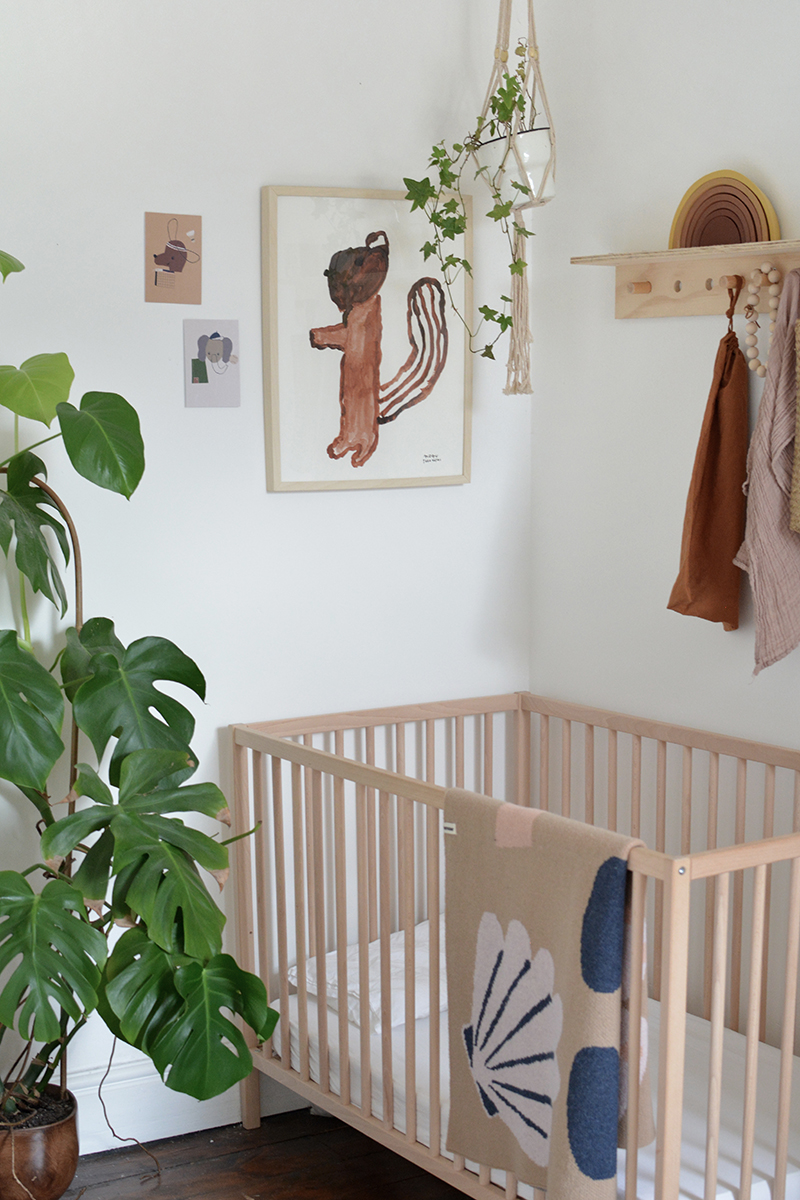gender neutral nursery with wall art and natural wooden cot