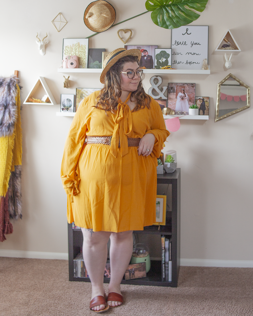 An outfit consisting of a straw boater hat, a yellow long sleeve bell sleeve with ties mini wrap dress with a wide brown braided belt and brown slide sandals.