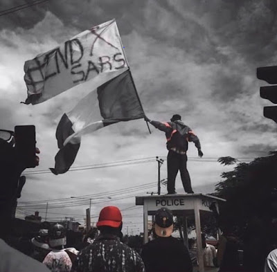 man holding nigerian flag and endsars flag during a protest
