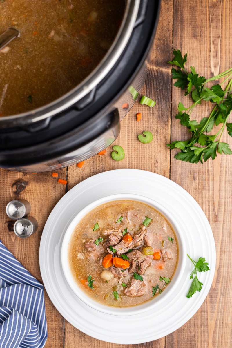 Overhead photo of Low Carb Instant Pot Pork Stew in the Instant por and in a white bowl both on a wooden table.