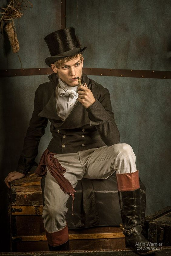 Man wearing Victorian aristocratic clothing. Top hat, double breasted jacket, trousers, boots, and smoking a pipe. Steampunk Victorian fashion and costumes for men