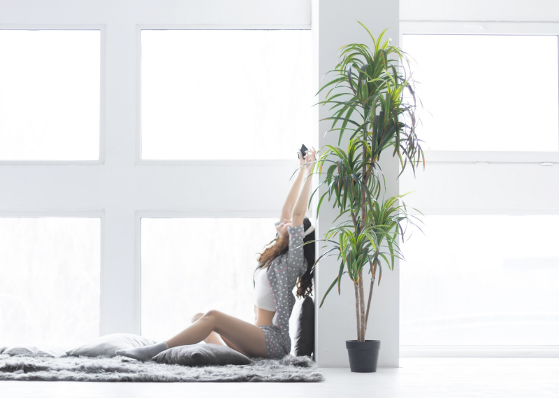 Lady stretching in bed with the sun coming through the window behind her in a post about at the benefits of creating a calming morning routine.