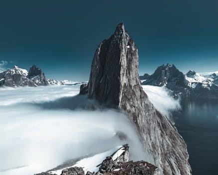 雲の絨毯の上に聳える切り立った山頂
