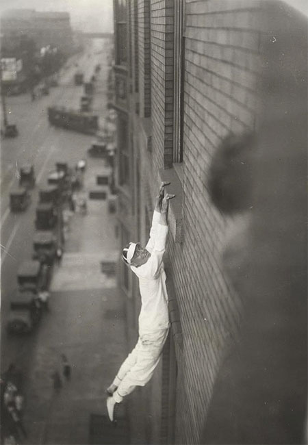 man-hanging-from-a-window
