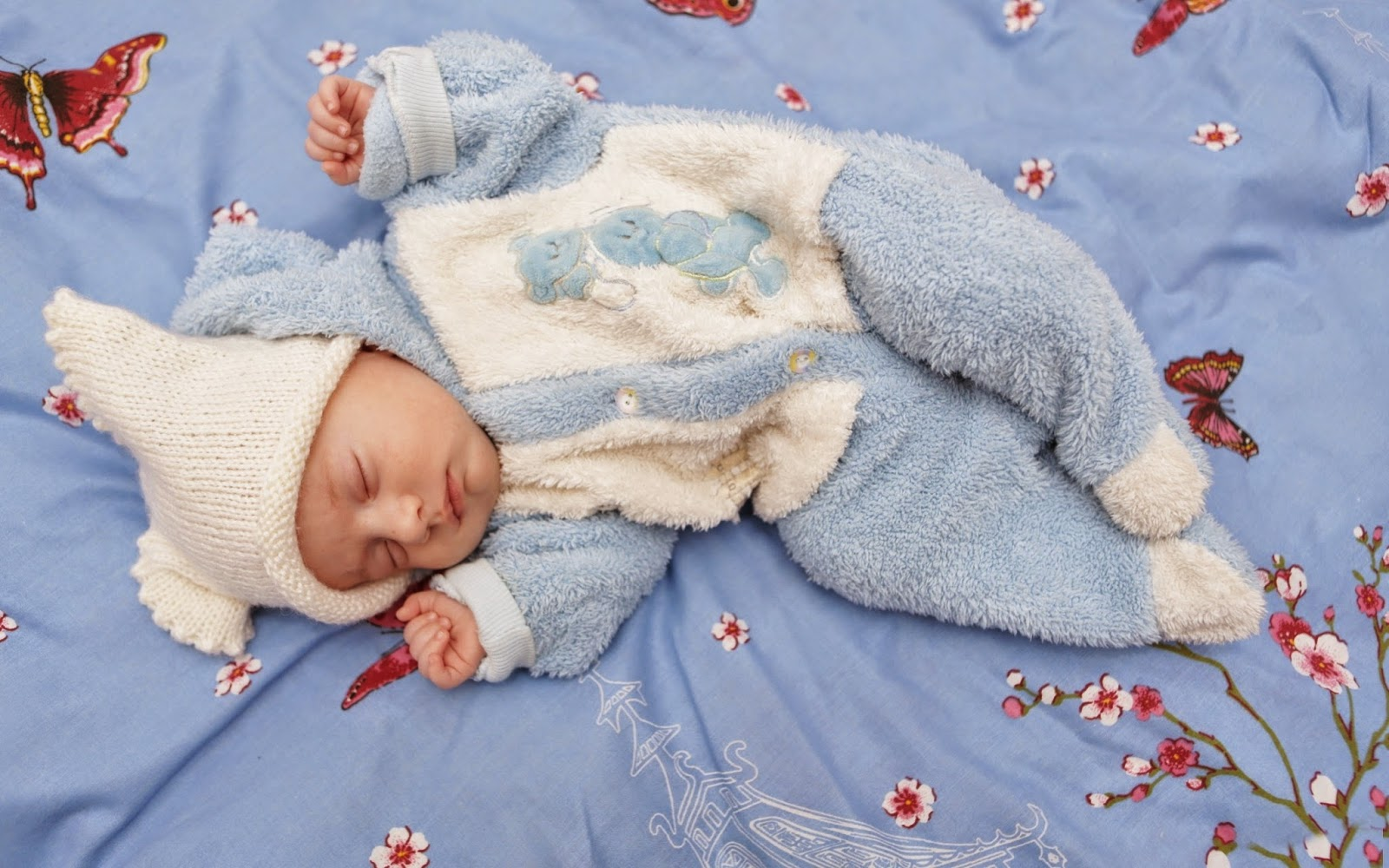 Baby-dressed_in-blue-white-sleeping-butterfly-sheet.jpg