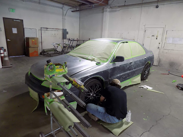 Almost Everything Auto Body technician masking a car prior to paint.