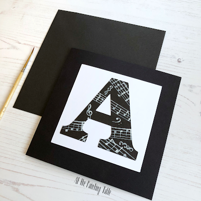 Black and white handpainted birthday card. The card has a large A painted with musical notes and symbols
