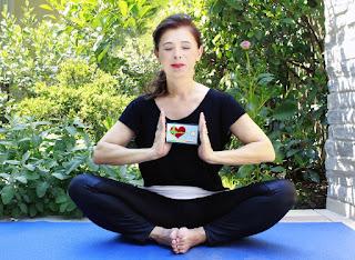 Woman in black leggings in yoga pose with phone app