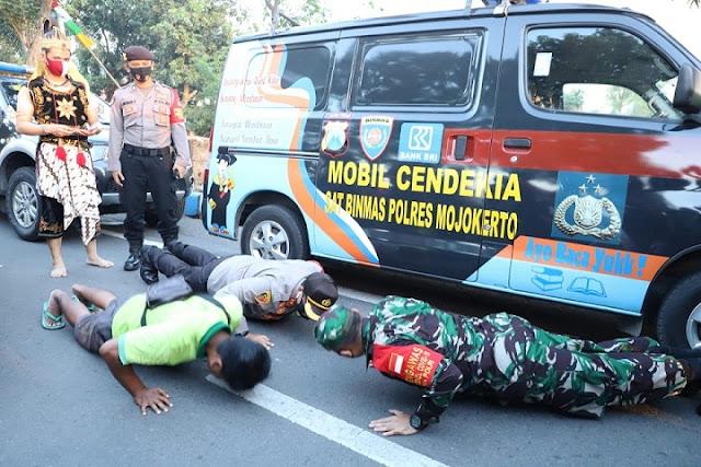"Mojokerto, -  Pendisiplinan protokol kesehatan terus digalakkan TNI–Polri di Mojokerto, Jawa Timur. Sejumlah ratusan personel TNI-Polri di wilayah Kabupaten Mojokerto secara serentak melakukan pendisiplinan protokol kesehatan.  Kegiatan pendisiplinan protokol kesehatan tersebut diawali apel gelar pasukan dalam rangka penanganan Covid-19 dan pendisiplinan protokol kesehatan, yang berlangsung di Lapangan Mapolres Mojokerto, Mojosari Kabupaten Mojokerto, Kamis (13/08/2020).   Usai apel dilanjutkan pemberangkatan pasukan gabungan TNI-Polri untuk melaksanakan pengawasan dan penegakkan disiplin masyarakat dalam mematuhi protokol kesehatan Covid-19, sebagai tindak lanjut dari Inpres Nomor 6 Tahun 2020 tentang peningkatan disiplin dan penegakkan hukum protokol kesehatan.   Dandim 0815/Mojokerto, Letkol Inf Dwi Mawan Sutanto, SH. saat dikonfirmasi, mengungkapkan, kegiatan pengawasan protokol kesehatan dilakukan TNI-Polri dengan mengerahkan seluruh perkuatannya, yakni Babinsa dan Bhabinkamtibmas guna menegakkan disiplin masyarakat dalam mematuhi protokol kesehatan Covid-19.  ""Kami bersama Polri melaksanakan pengawasan protokol kesehatan di seluruh wilayah Kabupaten dan Kota Mojokerto, yang tersebar di 21 Kecamatan dan dilakukan secara serentak guna mencegah dan menanggulangi persebaran Covid-19"" ungkapnya.   ""Kami tidak bosan memberikan himbauan agar masyarakat mematuhi protokol kesehatan Covid-19 utamanya pemakaian masker yang menjadi salah satu alat pelindung diri dalam memutus mata rantai persebaran Covid-19 di kalangan masyarakat. Bila ada yang melanggar, tentunya akan diberikan sanksi atau tindakan,"" tambahnya.  Pantauan di lapangan, Dandim 0815/Mojokerto Letkol Inf Dwi Mawan Sutanto, SH., bersama Kapolres Mojokerto AKBP Dony Alexander, S.IK., MH., tidak hanya menindak akan tetapi langsung memberikan contoh sanksi push up terhadap pengguna jalan yang tidak mengenakan masker. (Jayak)"
